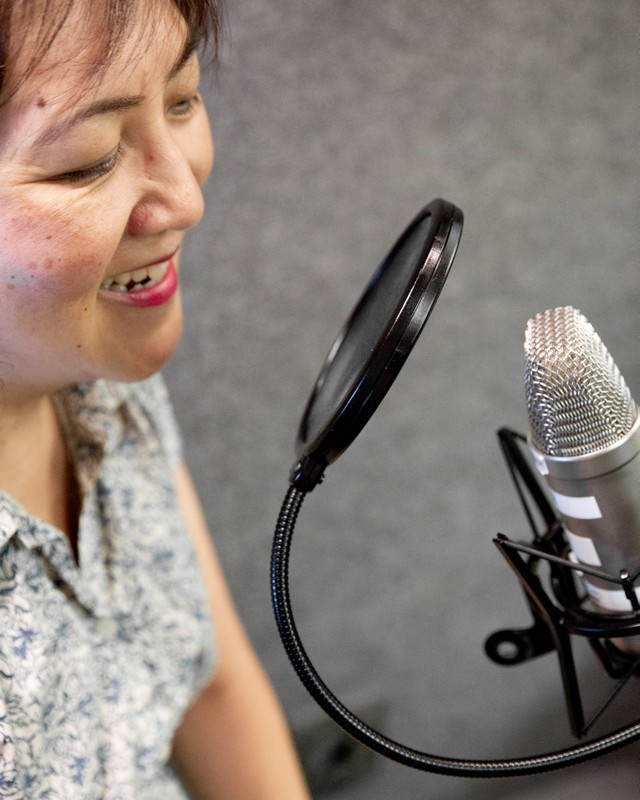 image description: Mona is smiling and seated infront of a microphone