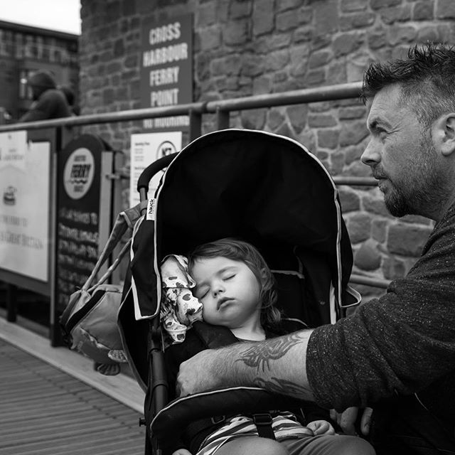 #1. Andy (38) & Ramona (2) - Waiting at the busy ferry dock  These guys caught my eye, Andy quietly whispering and stroking Ramonas cheek to soothe her as she tried to sleep amid the wind, rain and noise. Andy wants to instill a value of 'people not possessions' in his daughter and give her a love of 'good' music (think The Doors, Beatles and Bowie). Thanks for the conversation man, good to meet ya! #awesomedad #bristoldadproject #dontforgetdads #dadsofbristol