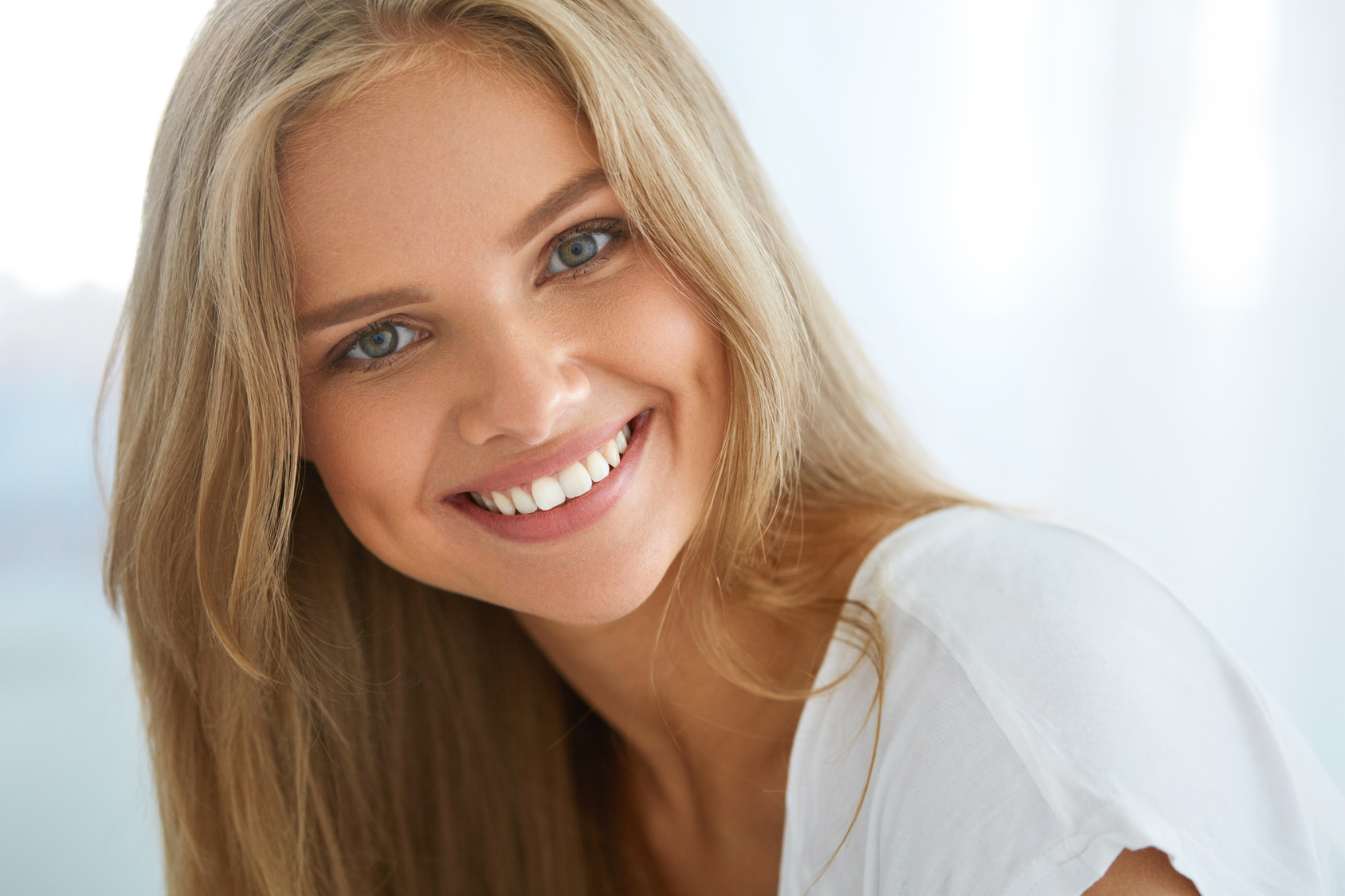 Attractive young lady enjoying beautiful teeth after a smile makeover at the dentist