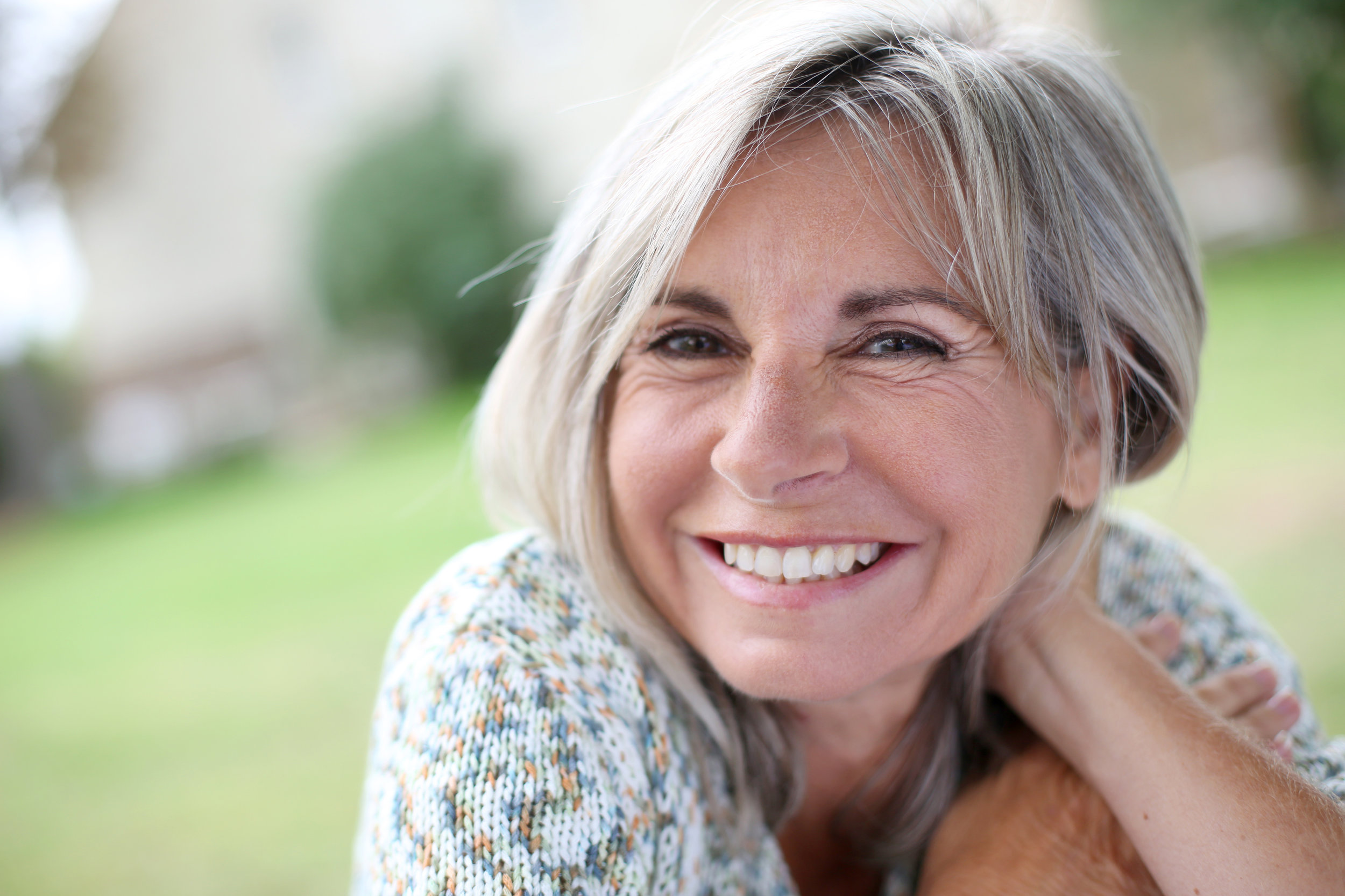 Lady in her 50s smiling after having dental crowns and veneers