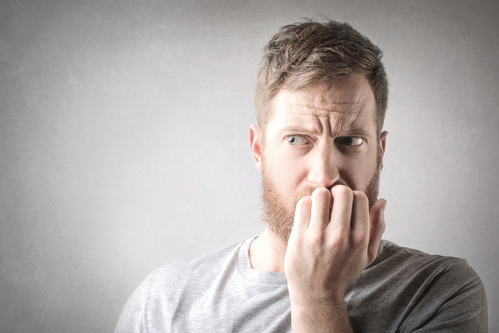 Man biting his nails and scared of going to the dentist