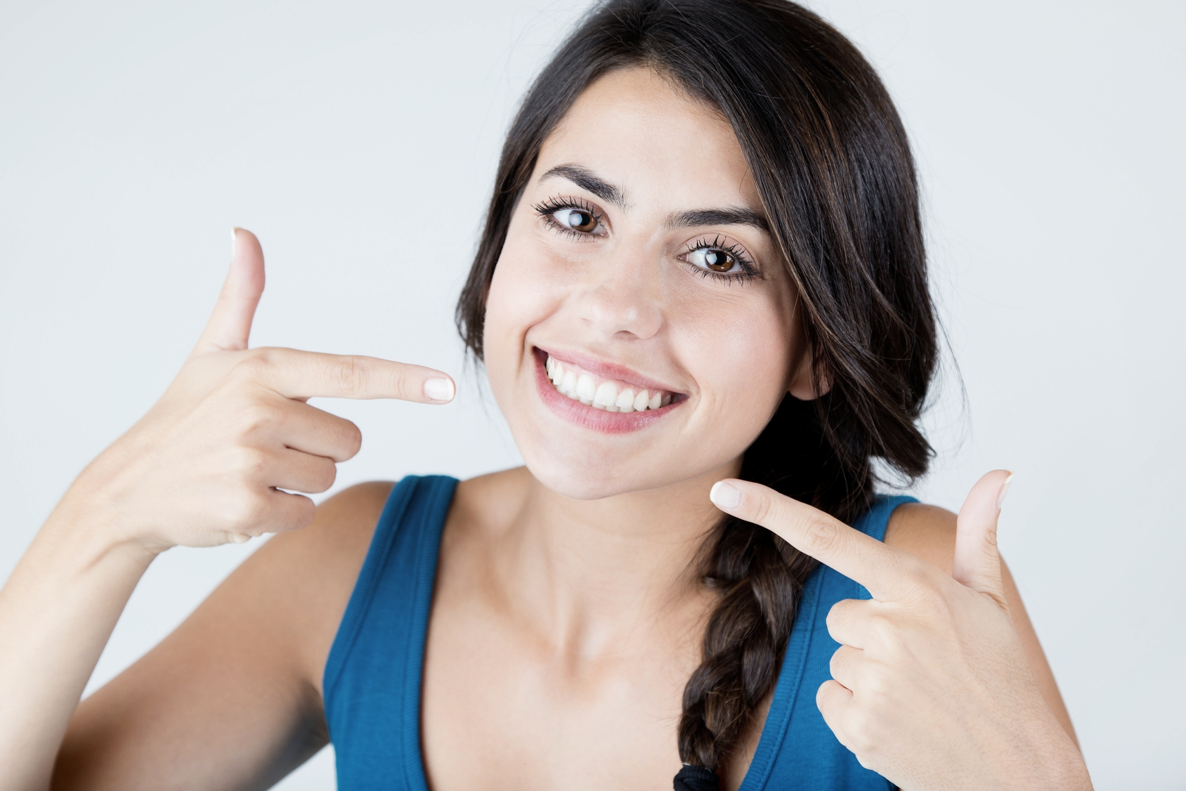 Young woman pointing to her beautiful teeth