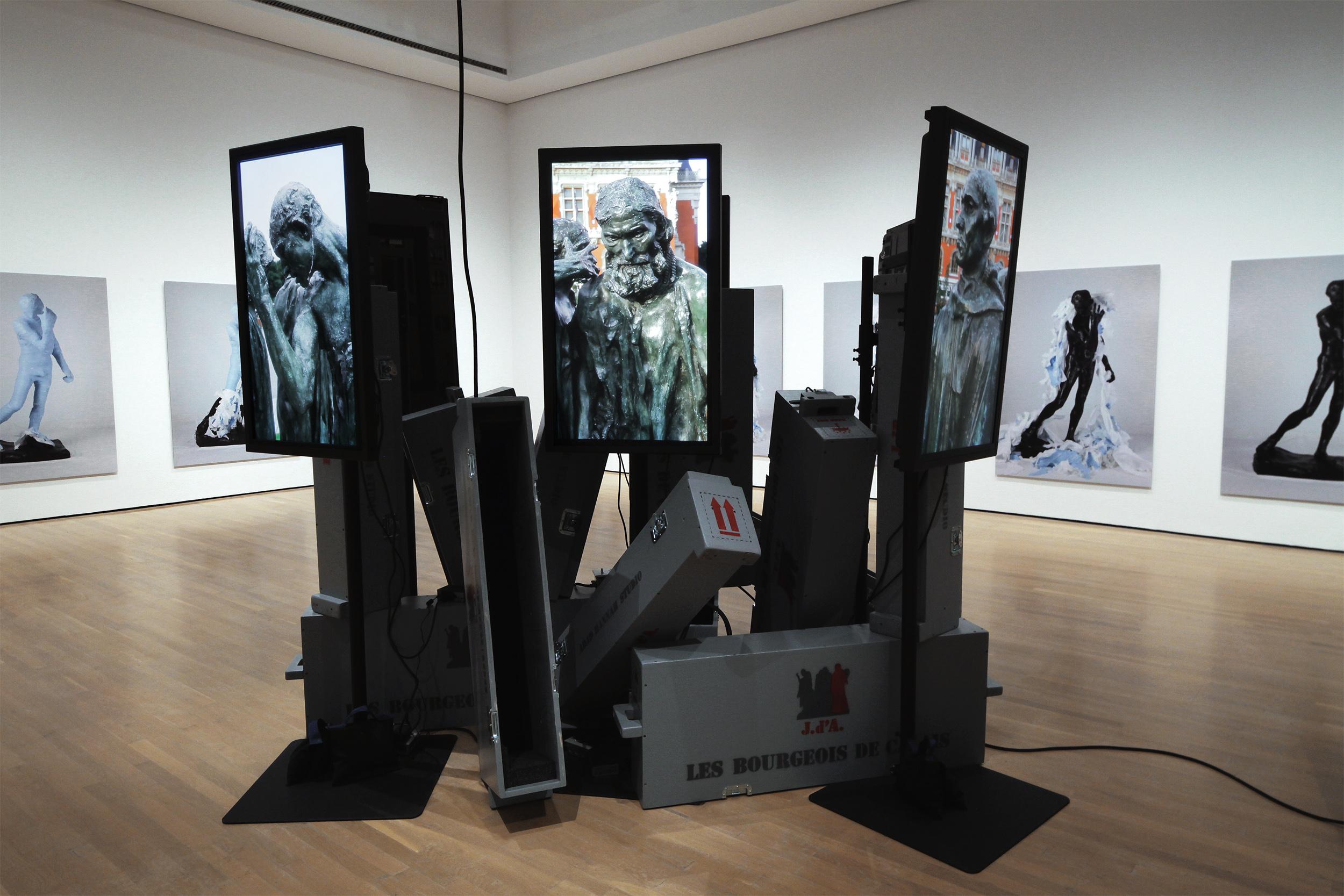 "Les Bourgeois de Calais: Crated and Displaced   2010, 7 HD Videos, 7 42"" plasma screens, 7 crates, other materials Installed at the Musée d'Art Contemporain de Montréal"