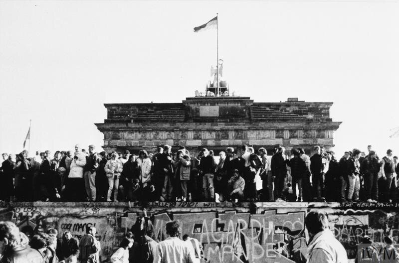 © Crown copyright. IWM (HU 73009)  East and West Germans celebrate the lifting of travel restrictions on East Germans on a graffiti covered section of the Berlin Wall in front of the Brandenburg gate, November 1989.