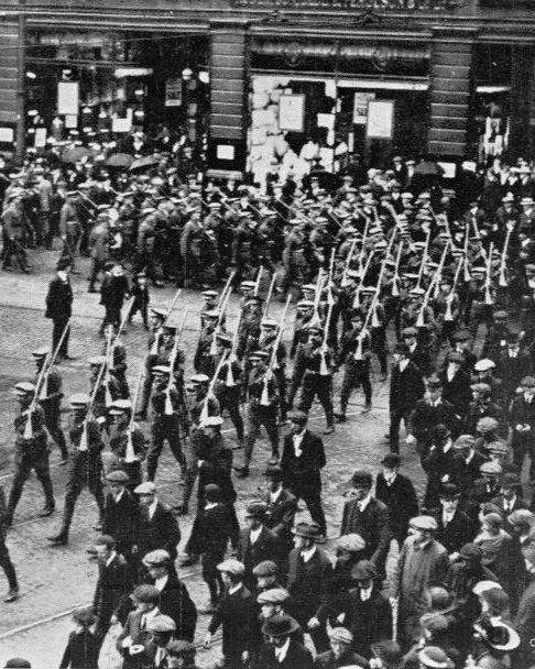 Formation of Groups - Members of the Ulster Volunteer Force march through Belfast, rifles on shoulders shortly before the First World War. © IWM (Q 81771)