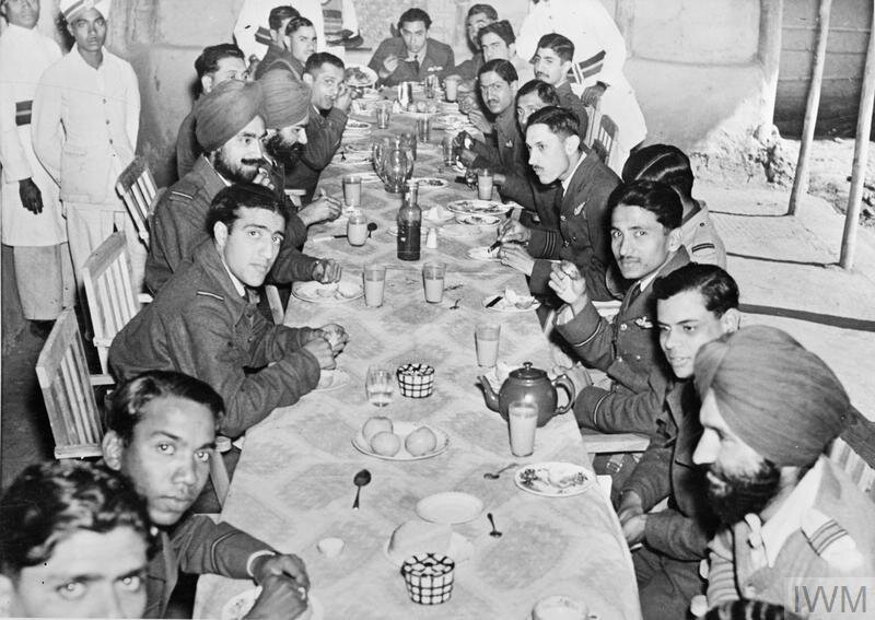Officers of No. 1 Squadron IAF sit down to tiffin in their mess at Imphal Main, India. At lower right sits 1 IAF's Commanding Officer, Squadron Leader Arjan Singh. © IWM (CF 112)