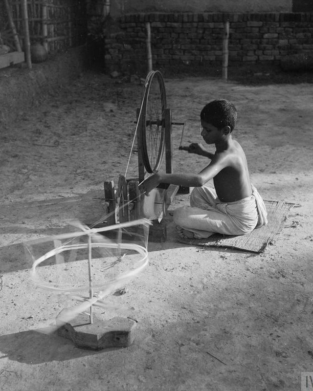 India 1944: A Bengali boy seated at his spinning wheel, his thread catching the sunlight © IWM (IB 1793)