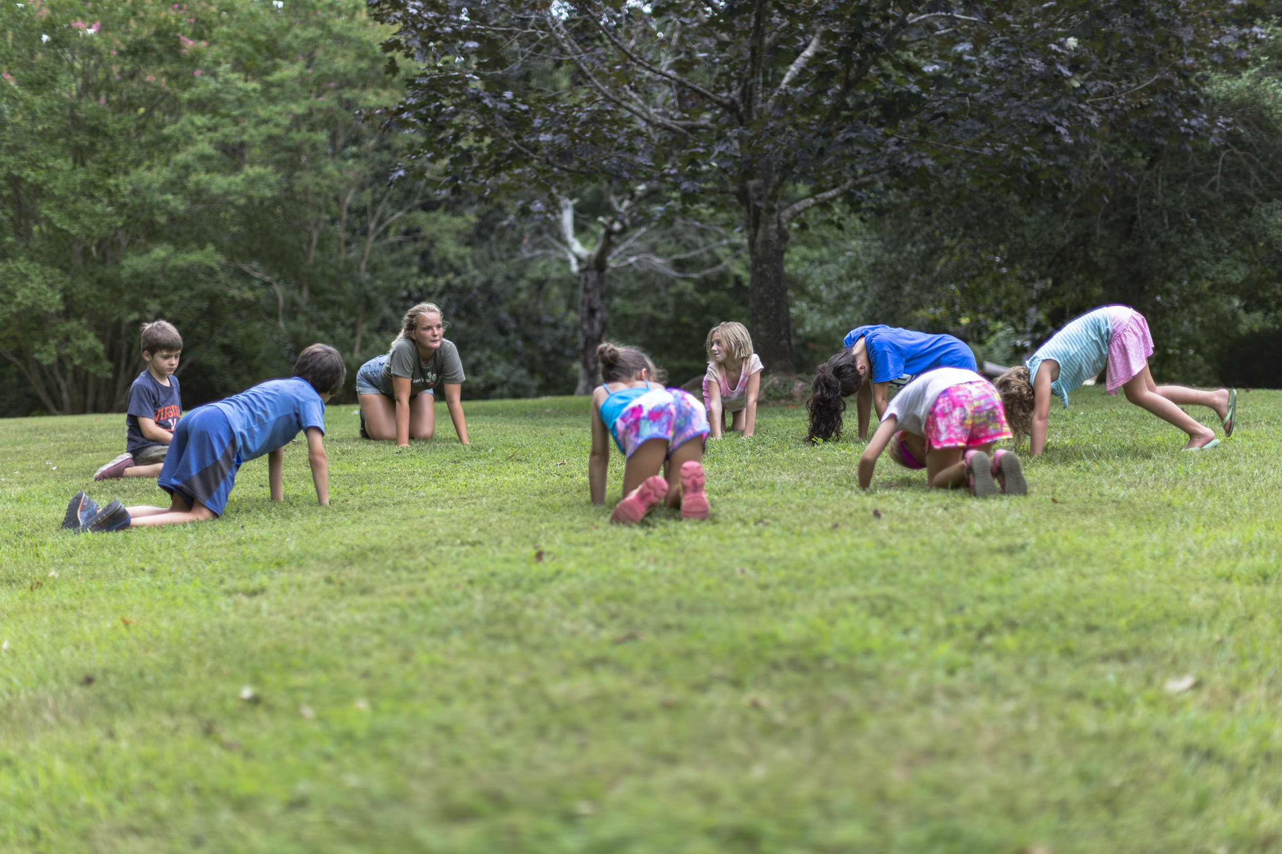 group of children play in grass at camp kumbayah in lynchburg virginia