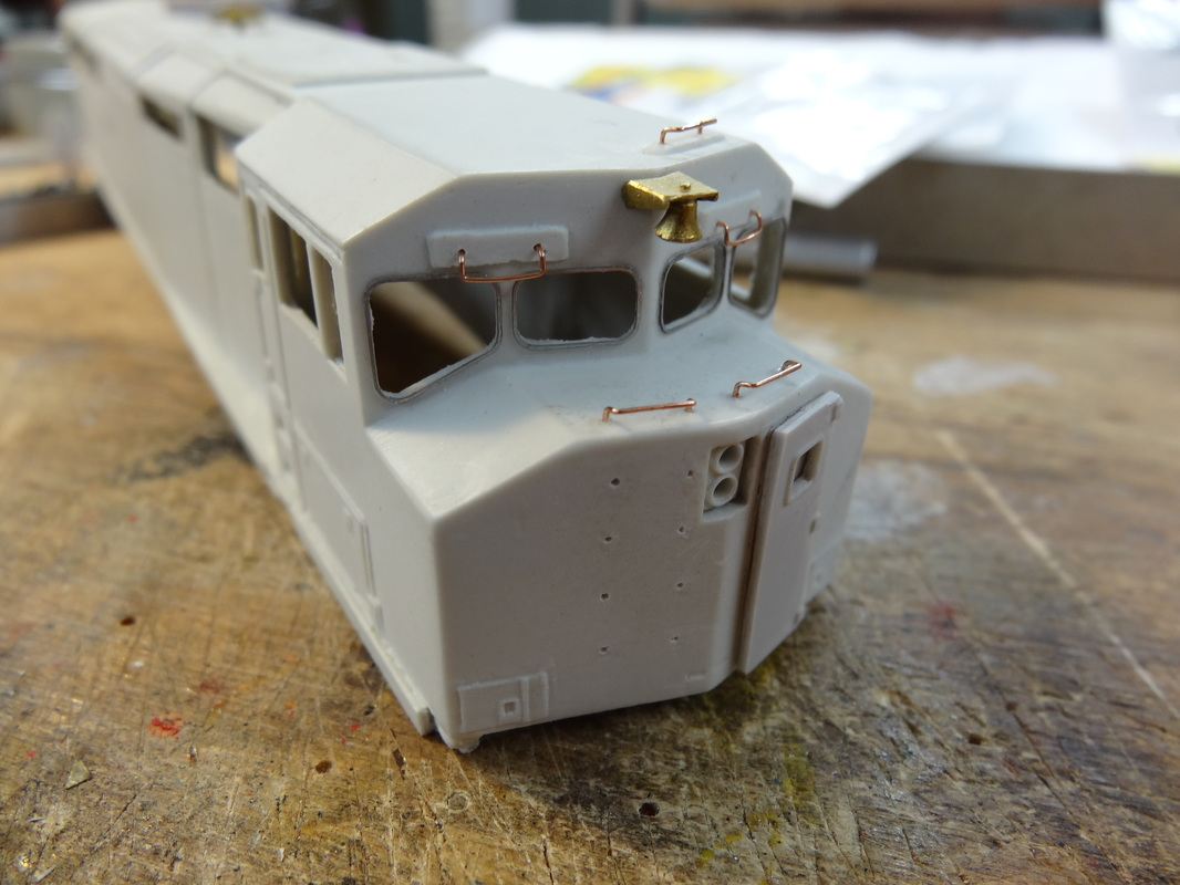 Nose-mounted bell and a few grabs, as well as the outside window frames. Notice I haven't put anything on the front, as the stripes have to be applies before anything else.