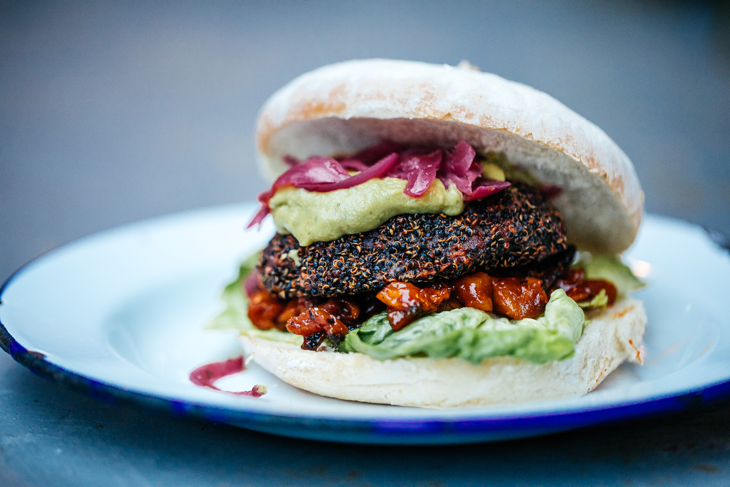BEETROOT & BLACKBEAN    Beetroot black bean patty, black quinoa seed coating, sriracha + pineapple salsa, lime infused red onion, lettuce, guacamole, ketchup