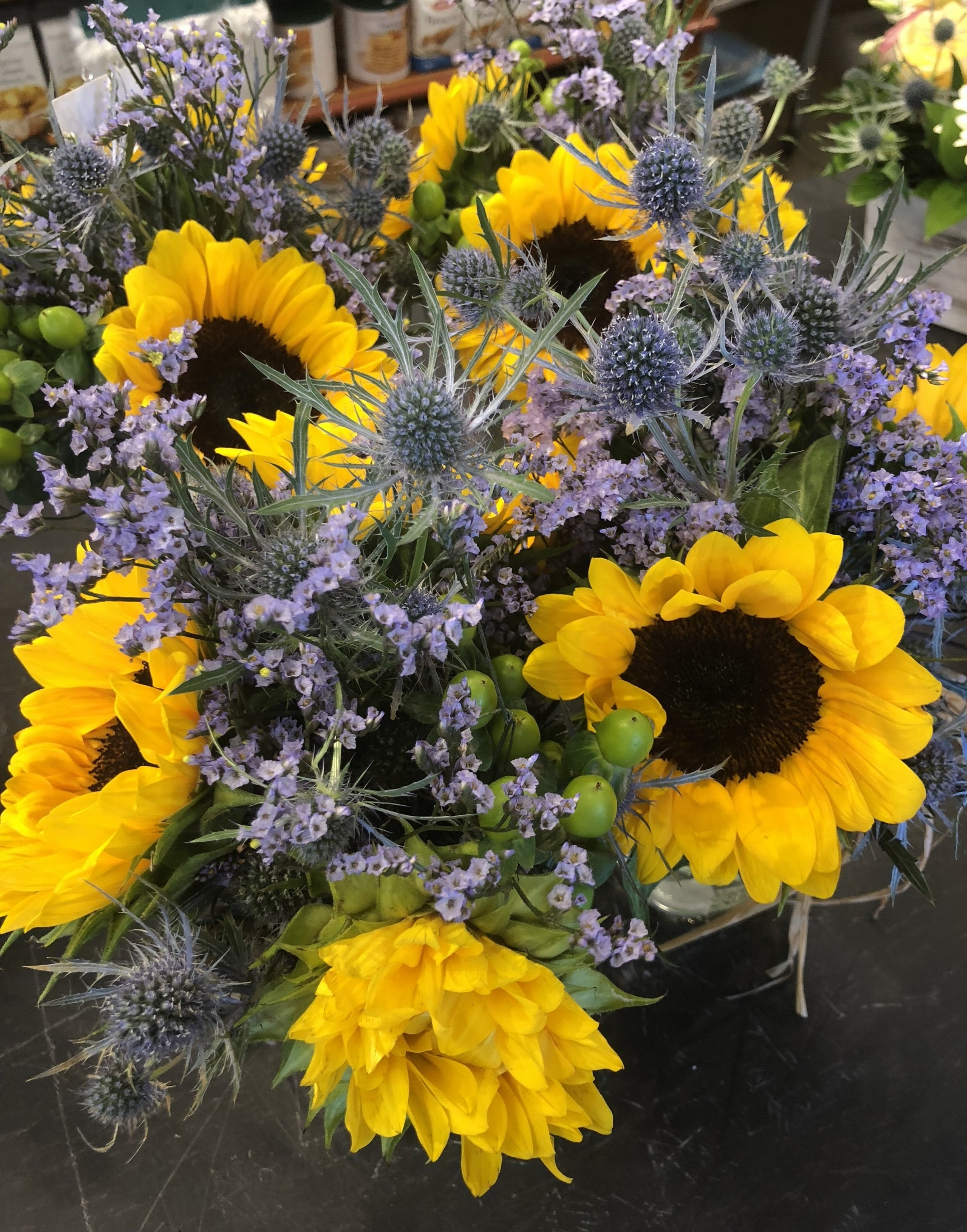 Russo's hand made floral arrangements of Sunflowers, Eryngium, Limonium and Green Hypericum berries