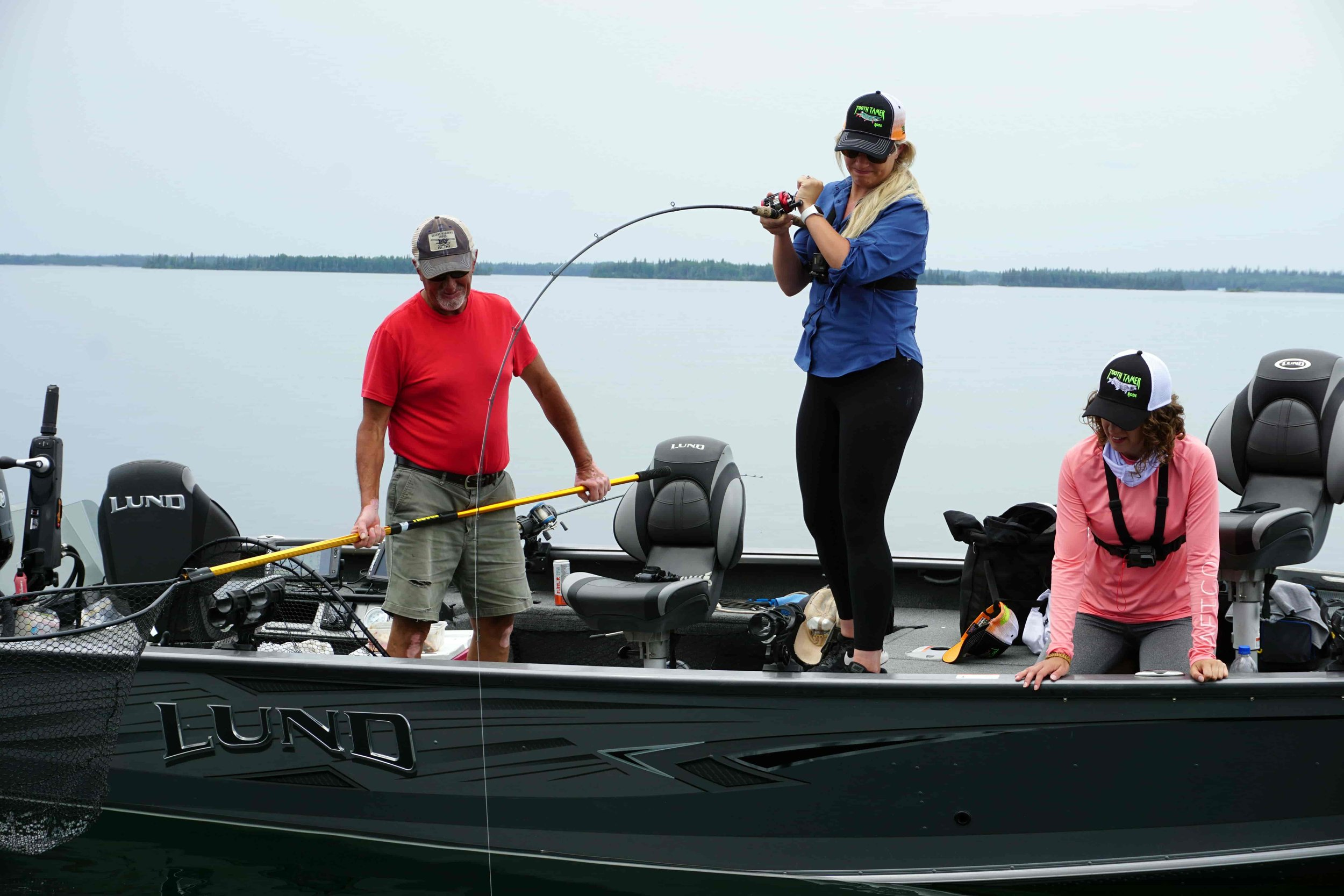 Nicole Stone pulling up a Lake Trout on Lake Athapapuskow while vertical jigging.