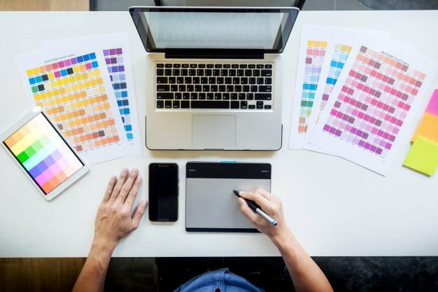 top-view-of-a-young-graphic-designer-working-on-a-desktop-computer-and-using-some-color-swatches-top-view_1423-139.jpg