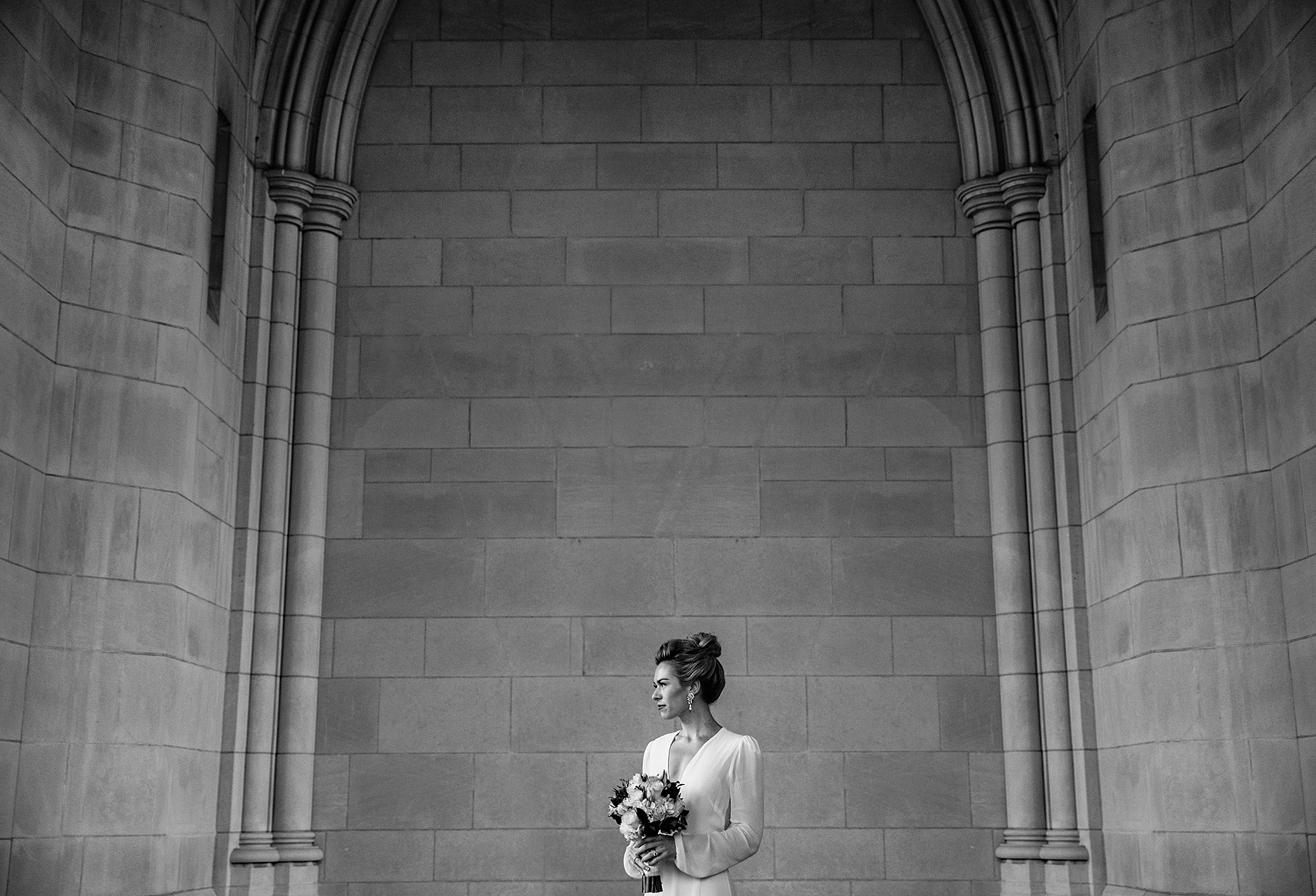 Bride stands in front of the National Cathedral in Washington DC, holding her bouquet