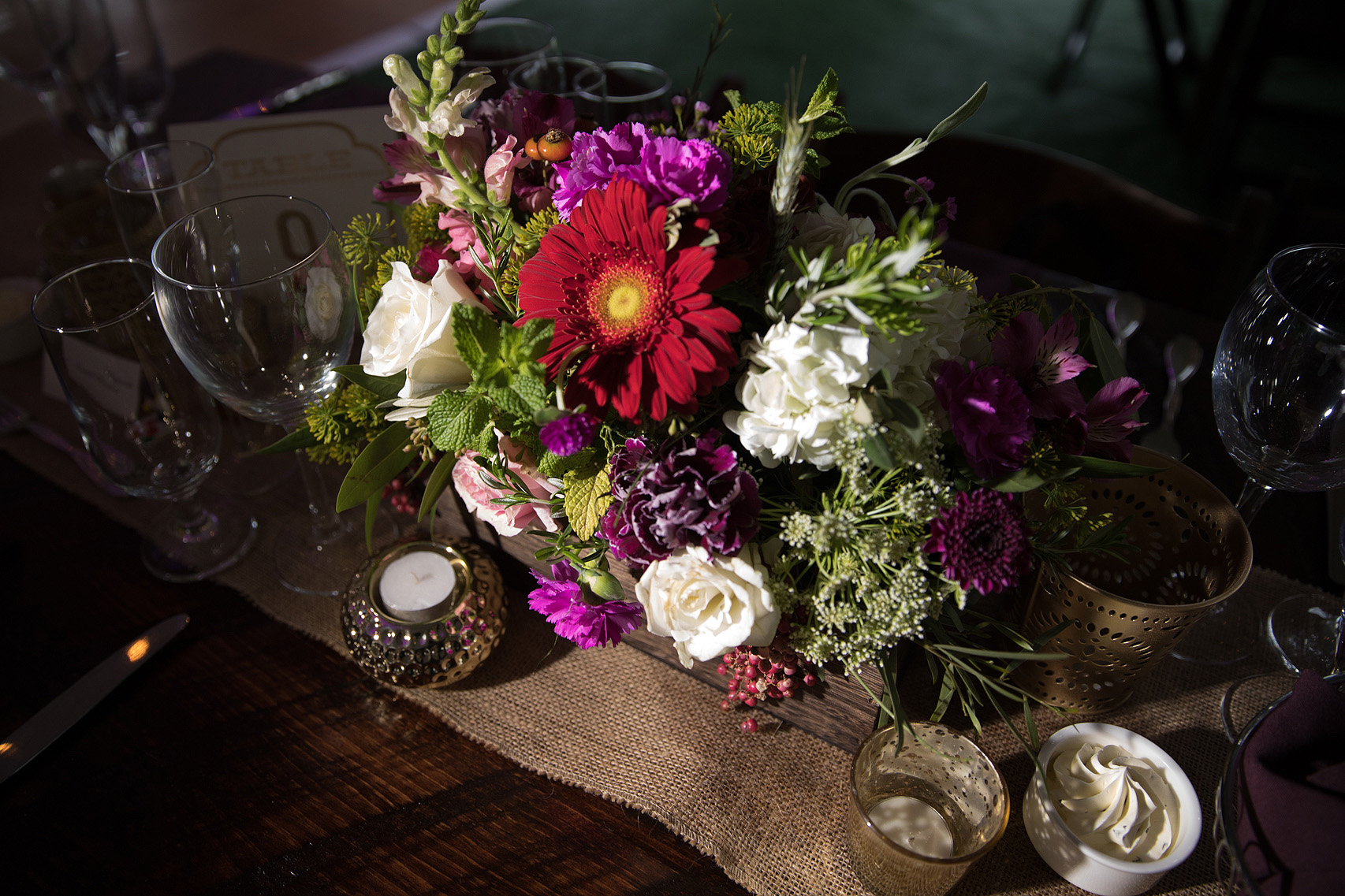 Colorful flower arrangement atop burlap runner at Virginia Vineyard wedding