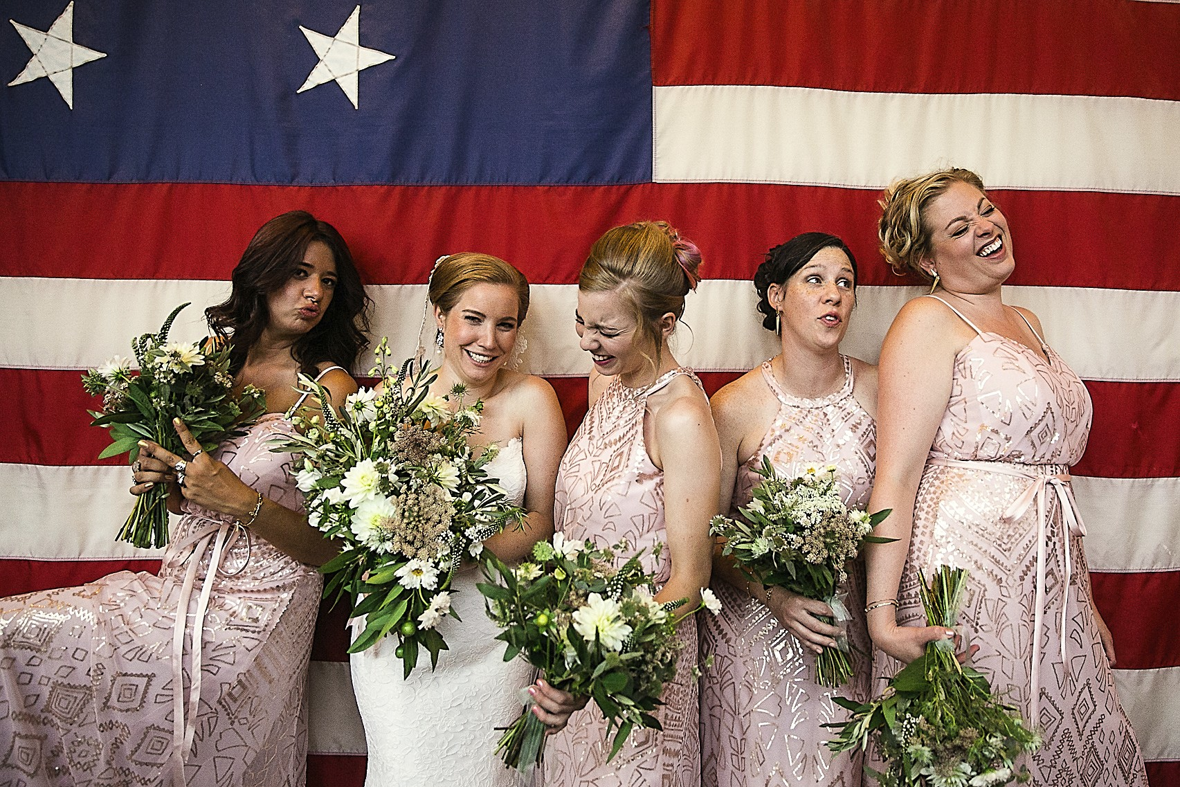 Bridal party posing in front of an old American flag at a Baltimore Museum of Industry wedding