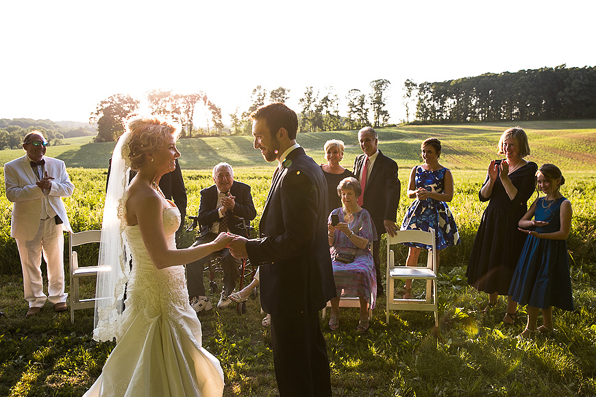 Bride and groom saying their vows in front of guest as the sun sets during a Maryland wedding