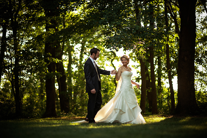 Bride and groom stroll along a forested area at sunset during a Maryland wedding