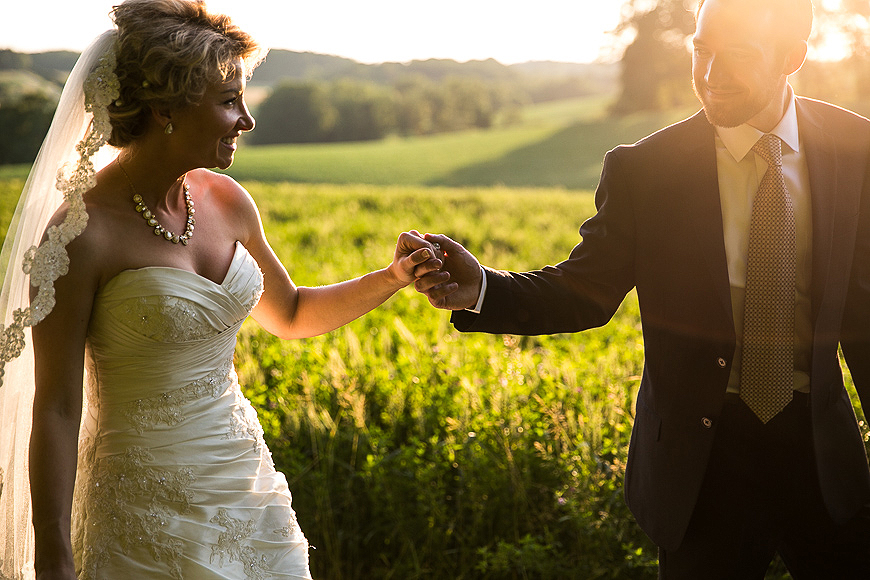 Bride and groom lovingly hold hands in a field in Northern Baltimore County on their wedding day as the sun sets