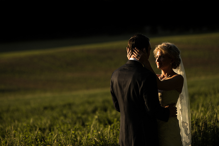 Wedding portrait in a green field at sunset