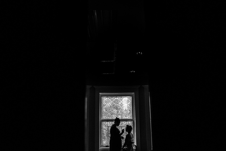 Bride silhouetted before an ornate window as she gets ready for her wedding at the Baltimore Engineers Club