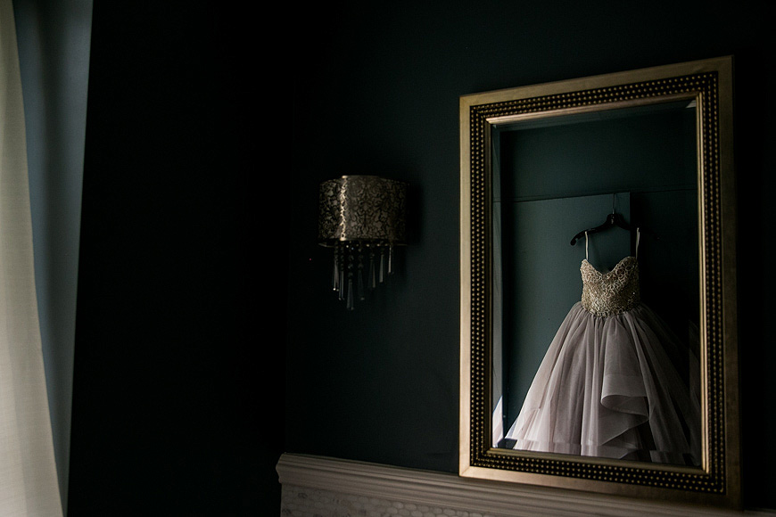 Wedding dress reflected in a gold-framed mirror