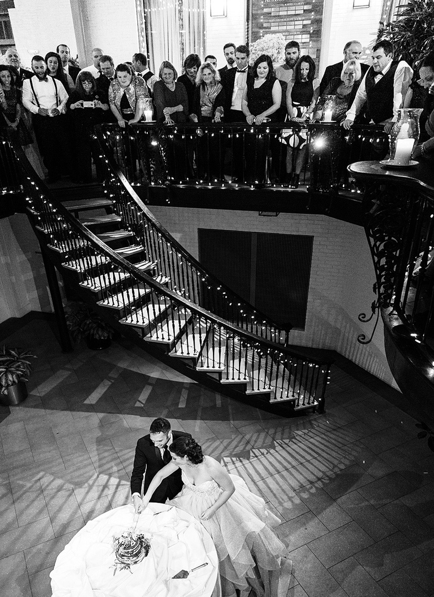 Bride and groom cut their wedding cake as guests look on from above at the Engineers Club