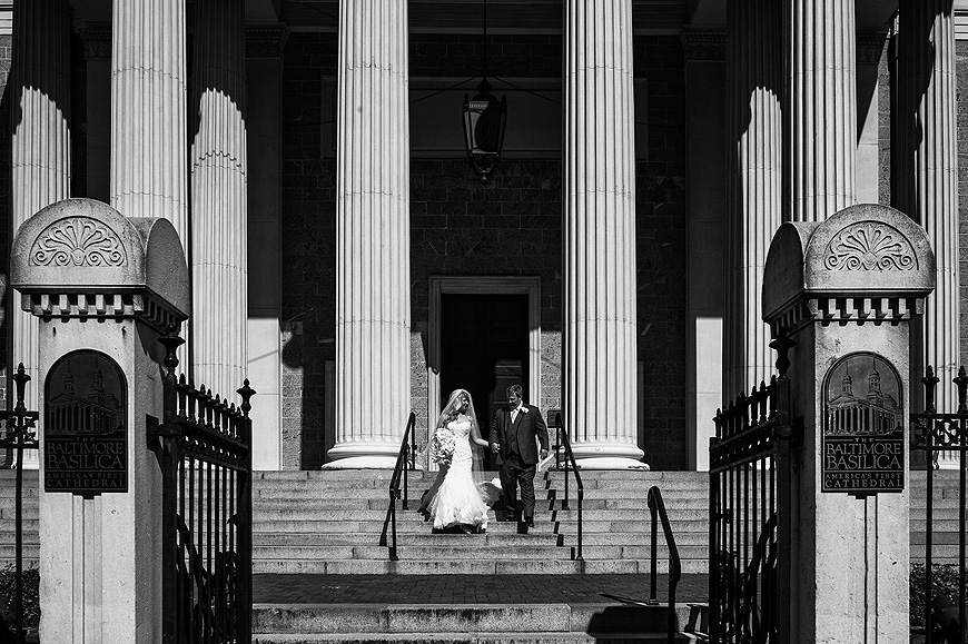 Newly married couple walking down the steps of the Baltimore Basilica after they are married
