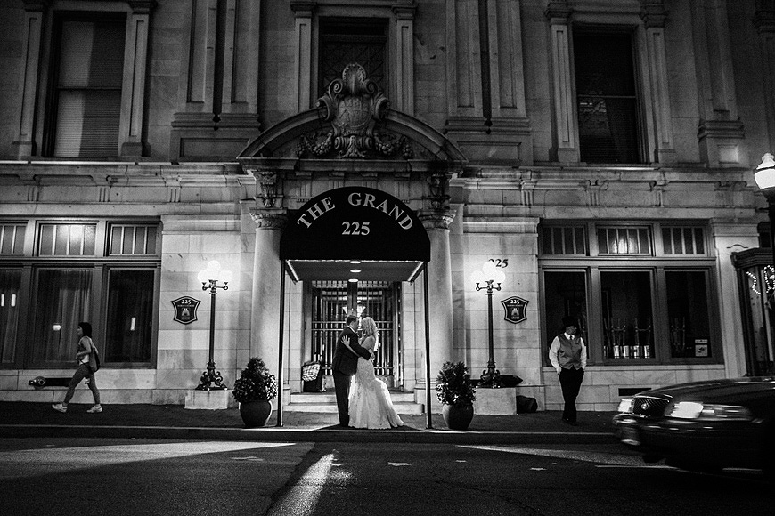 Bride and groom embracing under the awning in front of the Baltimore Grand Historic Venue on their wedding day