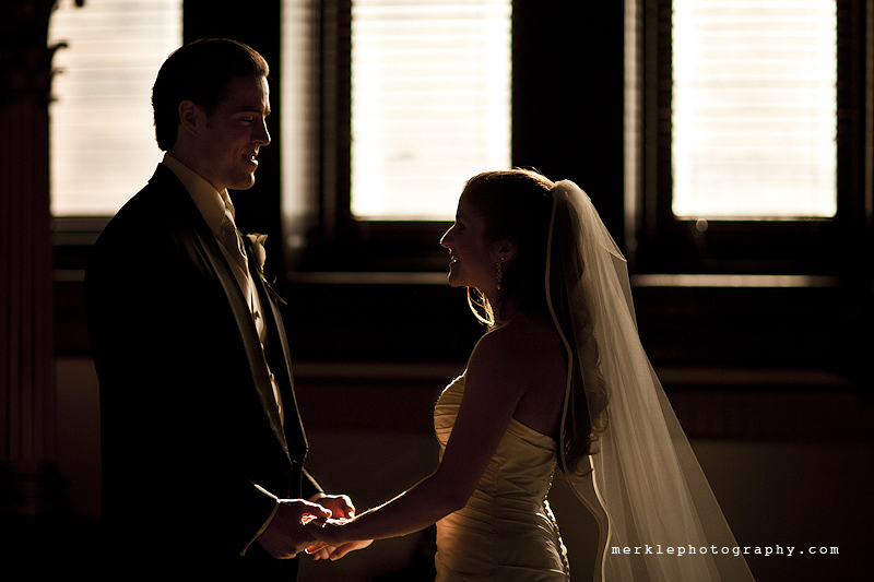Bride and groom facing one another and holding hands while lit by natural light in the Baltimore Grand Venue