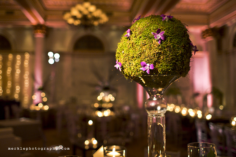Green moss topiary wedding decoration with purple flower accents