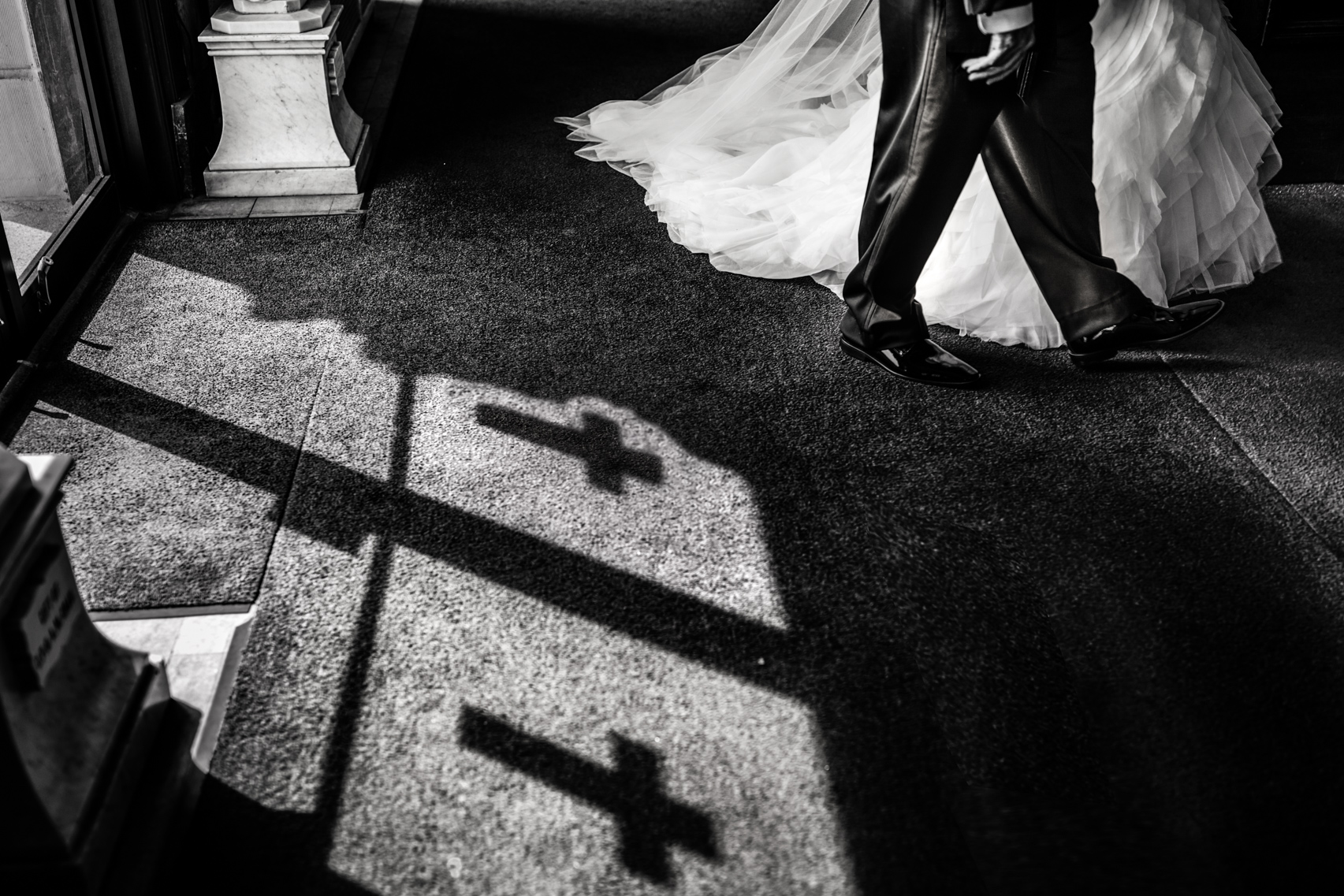 Bride entering church holding her father's hand with shadows of crosses on the ground