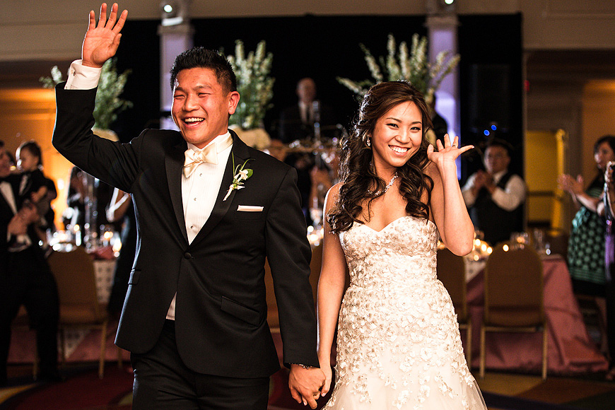Bride and groom enter their wedding reception and wave to guests