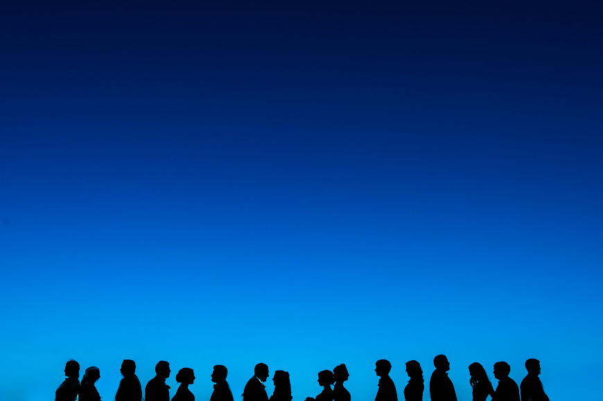 Wedding party silhouetted against deep blue sky