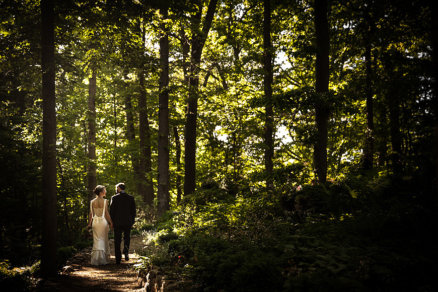 Bride and groom walking down a forested path at the Gramercy Mansion in Baltimore, Maryland