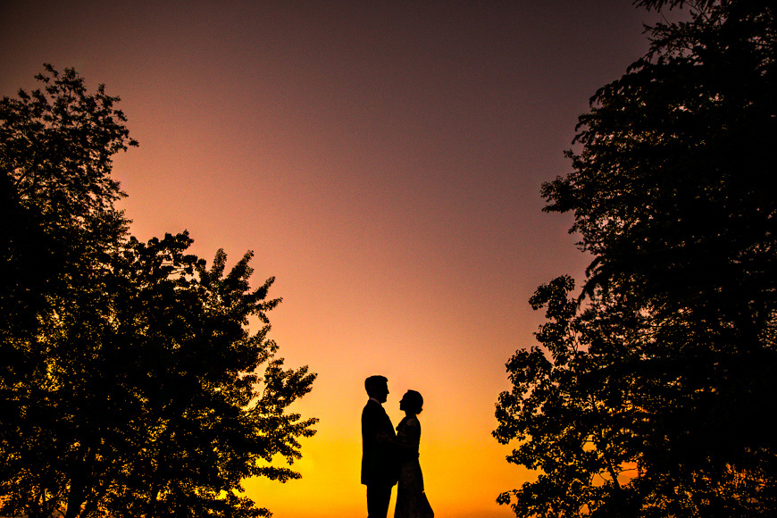 Bride and groom pose against the sunset sky after their Annapolis wedding