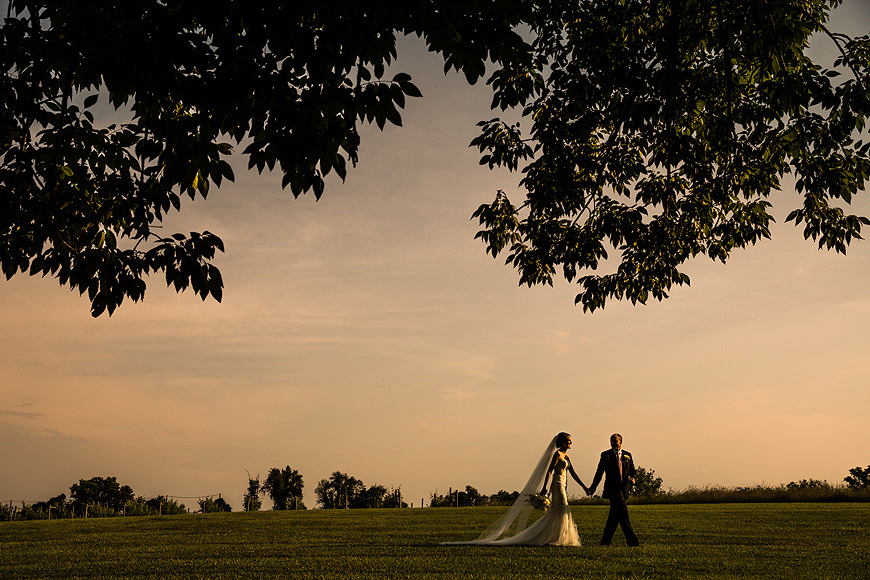 Bride and groom holding hands and walking across a field at sunset after their Stone Manor Country Club wedding