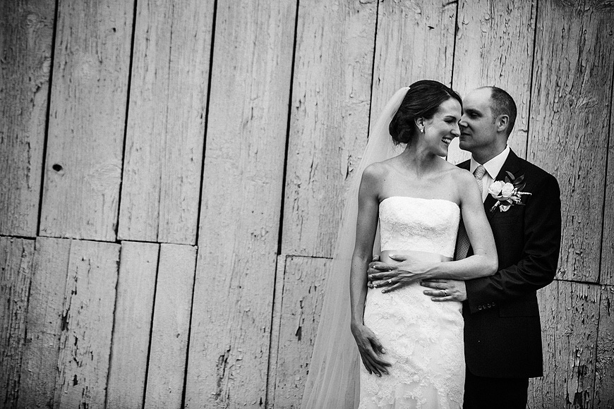 Bride and groom posing in front of a weathered wood barn at Stone Manor