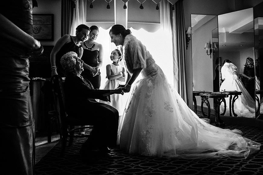 Bride leaning over to hold hands with her grandmother on her wedding day at the Maryland Club