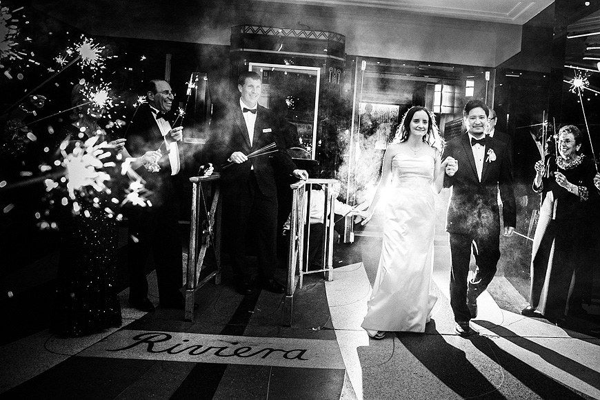 Wedding guests hold sparklers as the bride and groom exit the historic Riviera Theater in Charleston SC