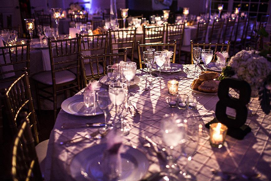 Table settings at wedding reception under moody light at Morais Vineyards