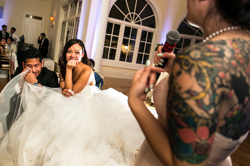 Wedding couple listening to toasts during wedding reception at Morais Vineyards; groom wiping away tear with brides dress