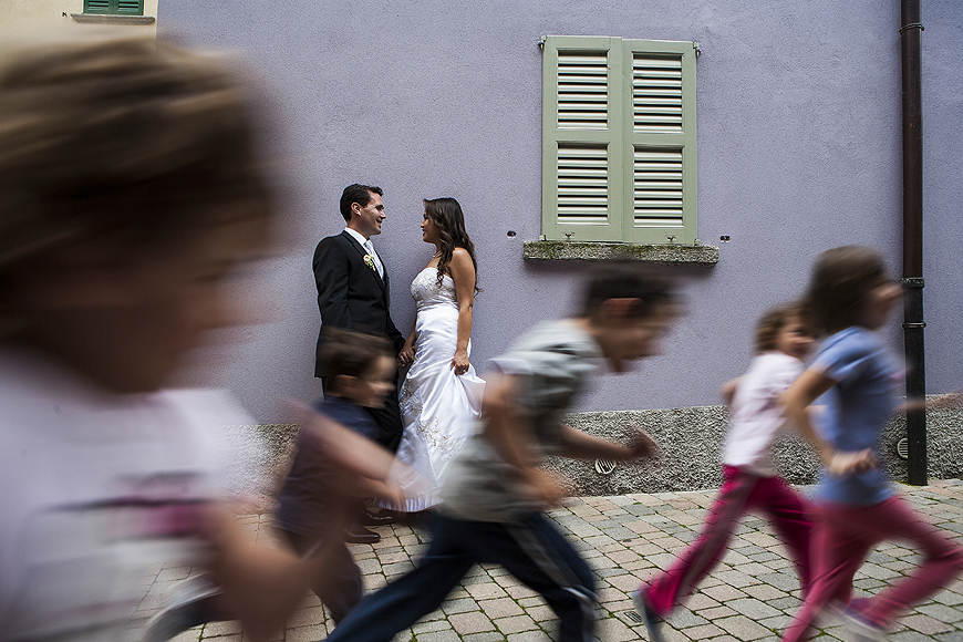 Bride and groom posing in Lake Como Italy as children run down the street