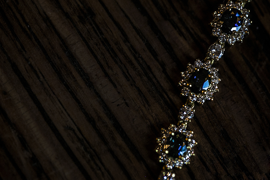 Sapphire and diamond bracelet against dark wood background in natural light at Greenville Country Club wedding