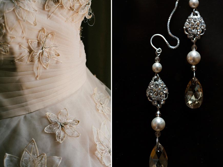 Wedding dress and earrings against black background