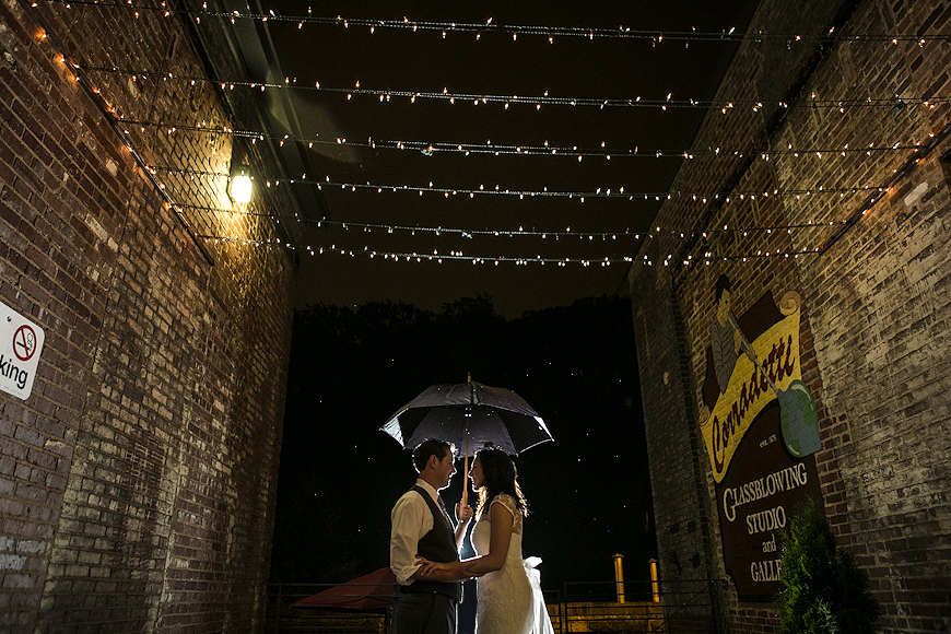 Bride and groom in the rain under umbrella cover at Woodberry Kitchen Baltimore