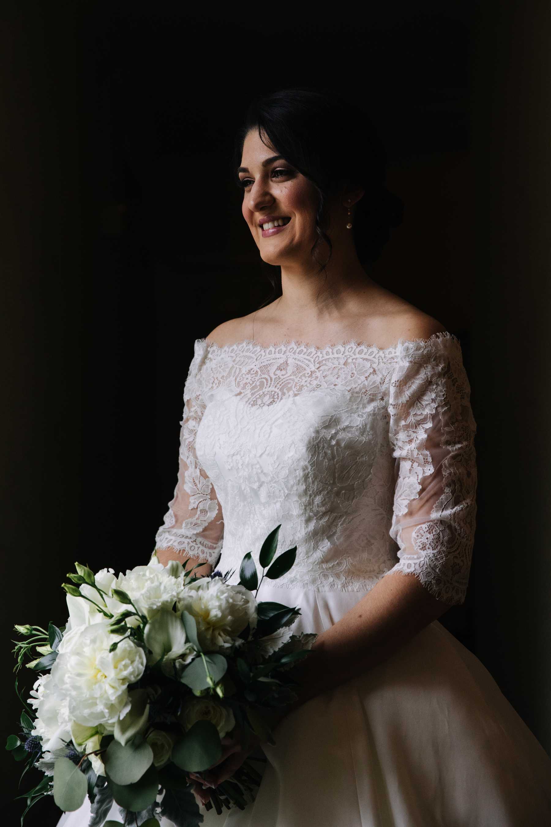 Bride in window light holding a white bouquet before her wedding
