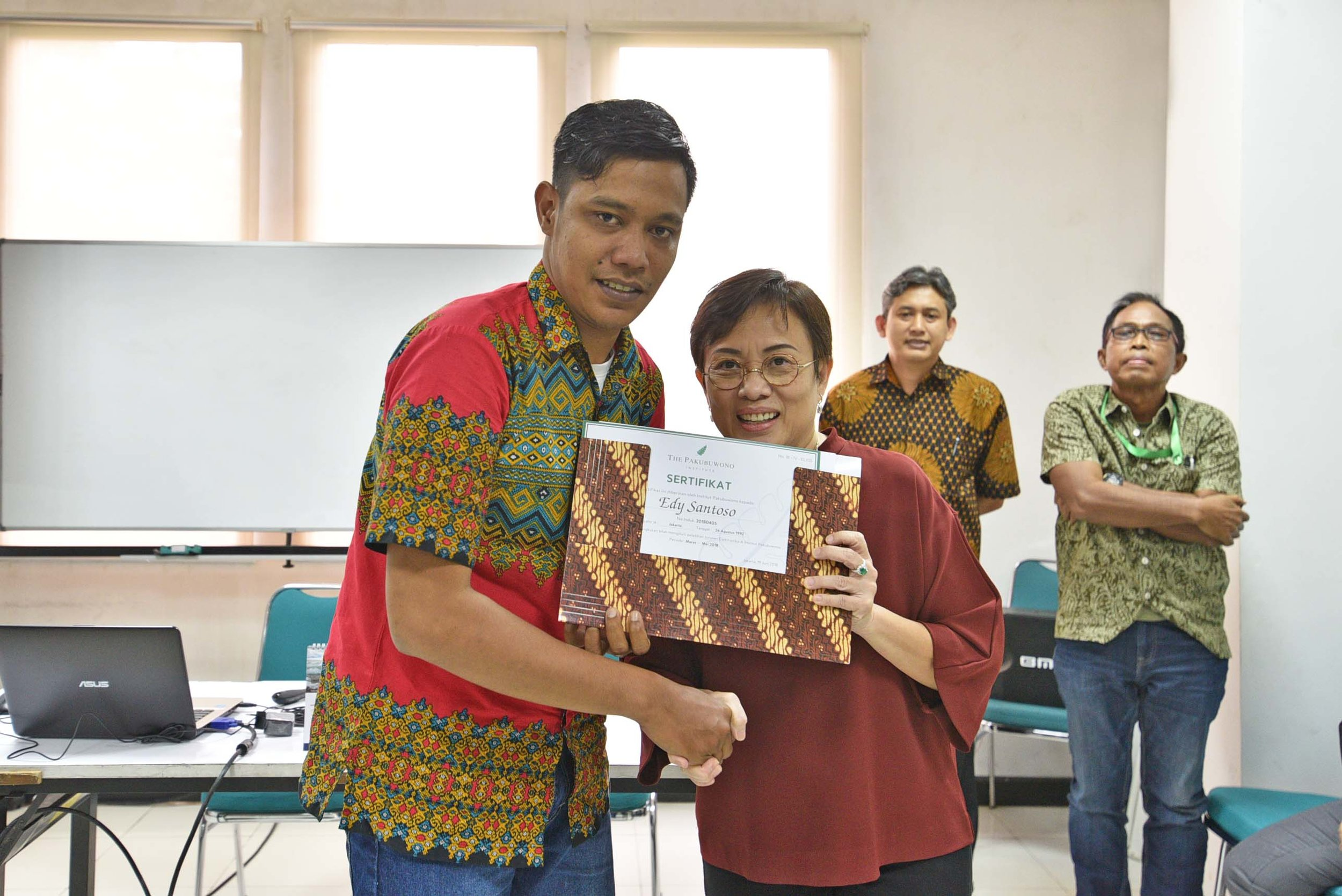 (Mrs. Anisa Himawan handed the certificate to one of the Top Ten graduate with the highest grades)
