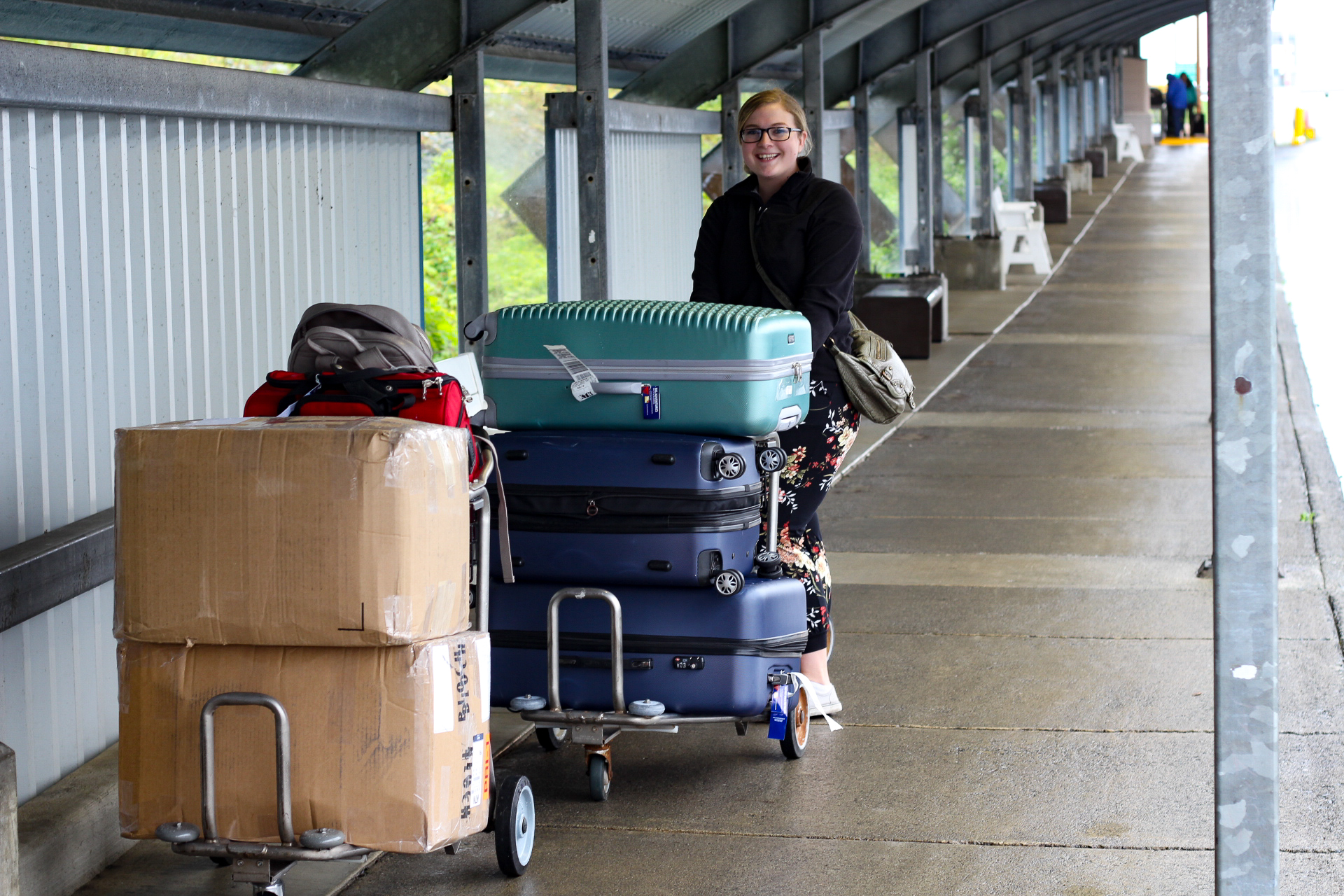 My co-worker Bailey and our very large pile of Suitcases (There are another 2 suitcases on a trolley behind Bailey)