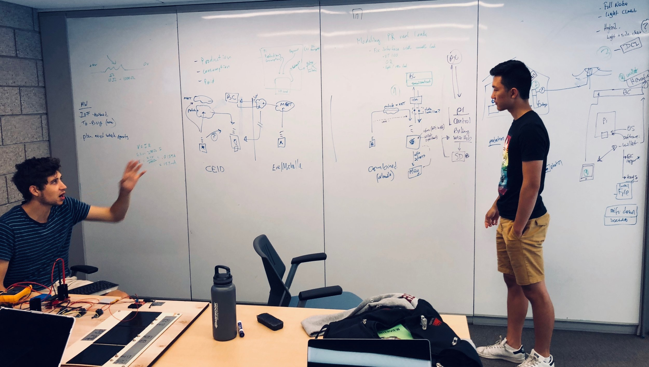 Students Jonathan Simmonds (hardware lead) and Eric Duong (software lead) discuss a prototype to deploy community solar microgrids in Puerto Rico. (At Yale CEID)
